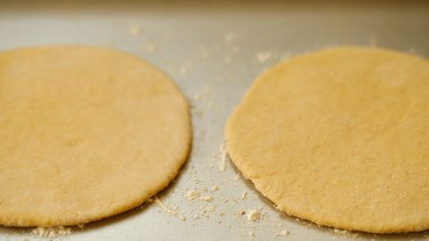 two rolled discs placed in the hot baking tray with some flour already sprinkled on the tray