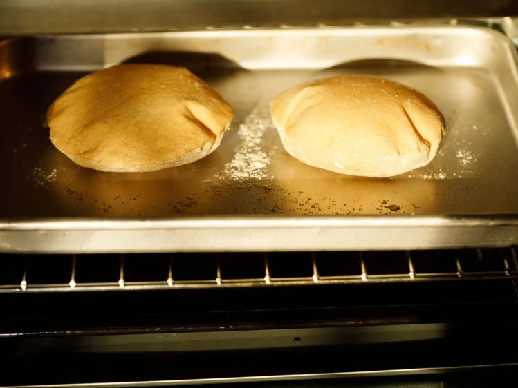 pita breads baking and puffing in the oven
