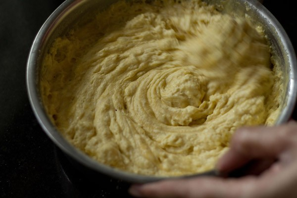 frothy bubbly khaman batter being whisked