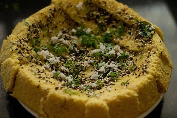 khaman dhokla garnished with coconut and coriander leaves
