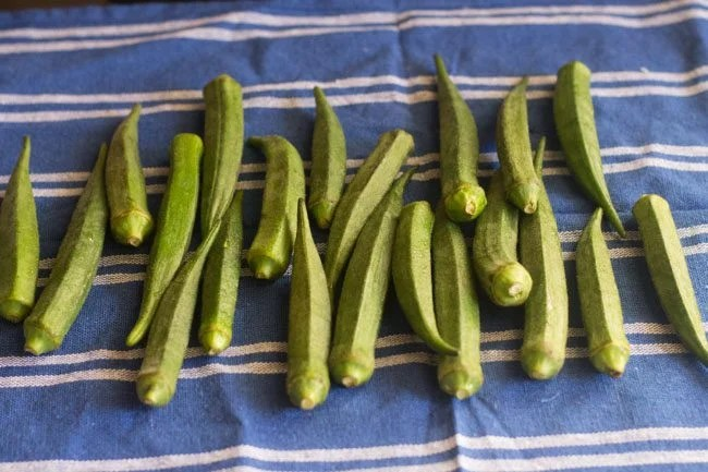drying okra on a kitchen napkin to make  bhindi ki sabji