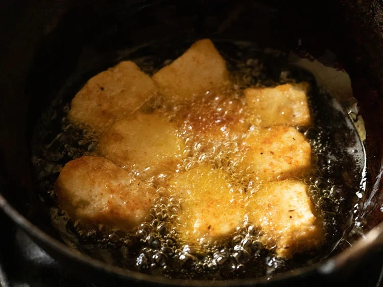 frying paneer cubes in oil in a pan