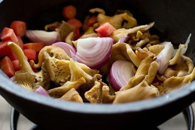 sliced onions, oyster mushrooms, carrots and veggies in a pot.