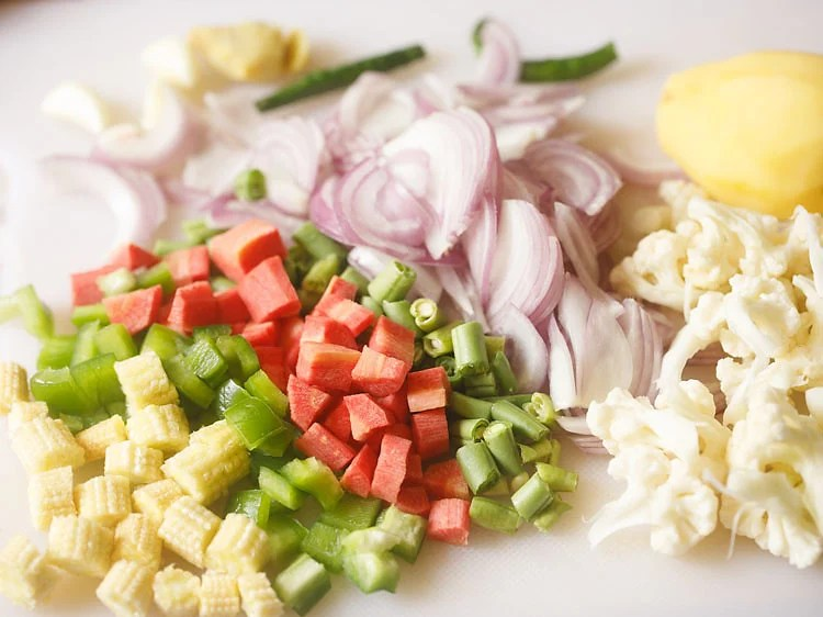 sliced onions, chopped bell pepper, carrots, cauliflower, green beans on a chopping board