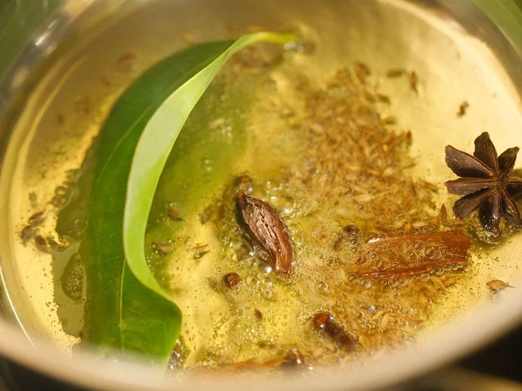 adding whole spices to the hot ghee
