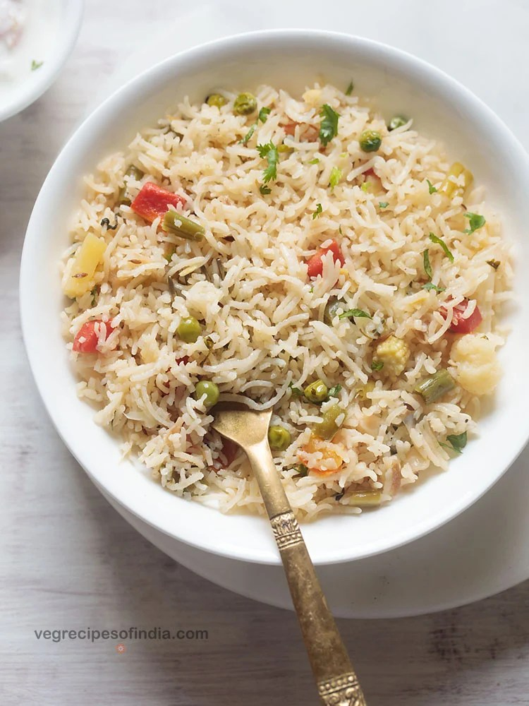 vegetable pulao served in a white shallow bowl with a brass spoon in the pulao