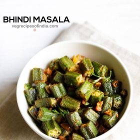 bhindi masala in a white bowl on a off white napkin on a white background