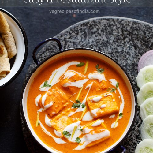 paneer butter masala served in a navy blue rimmed white small pan. garnished with cream and cilantro. side of sliced cucumber and onions at the side.