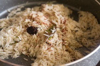 saffron threads added to rice and spiced oil mix