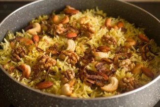 Kashmiri pulao topped with fried onions and nuts in the cooking pan