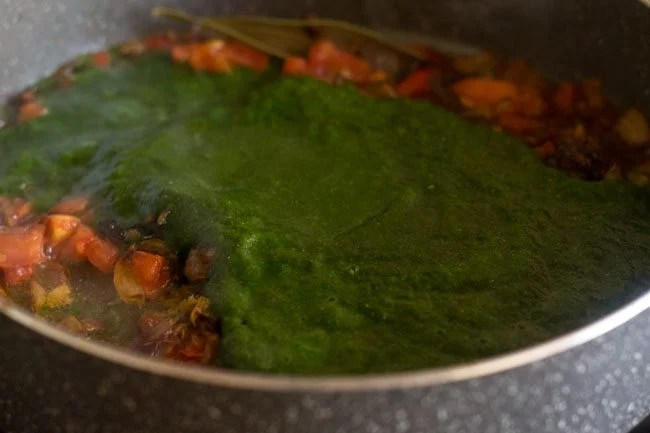 adding palak puree for palak biryani