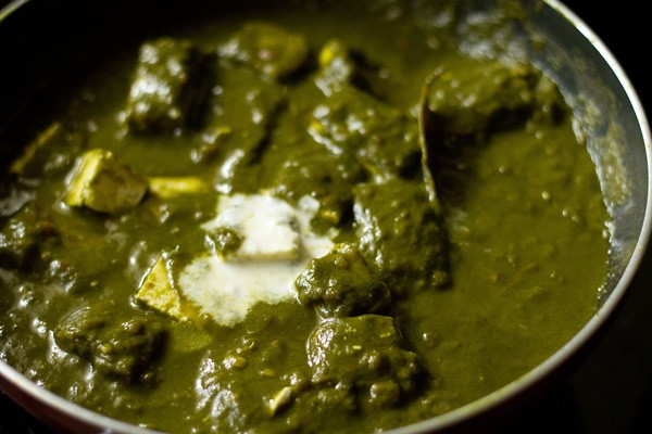 adding cream to palak paneer recipe