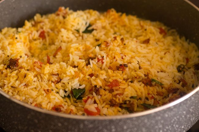 mixing cooked rice with masala