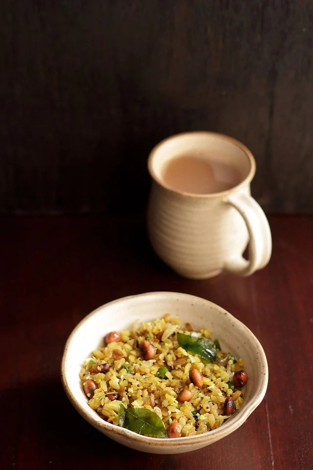 kanda poha served in ceramic bowl with a side of Indian chai in a ceramic mug