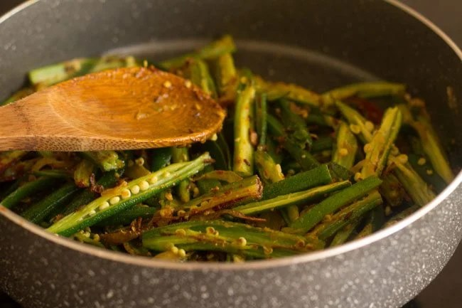 mixing spices with lahsuni bhindi