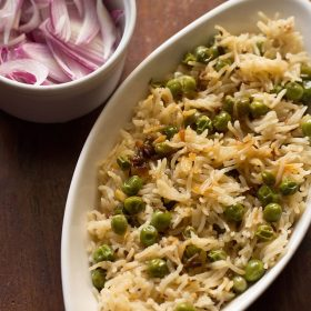 peas pulao served in a white oval serving plate with a white bowl of sliced red onions on a brown wooden board