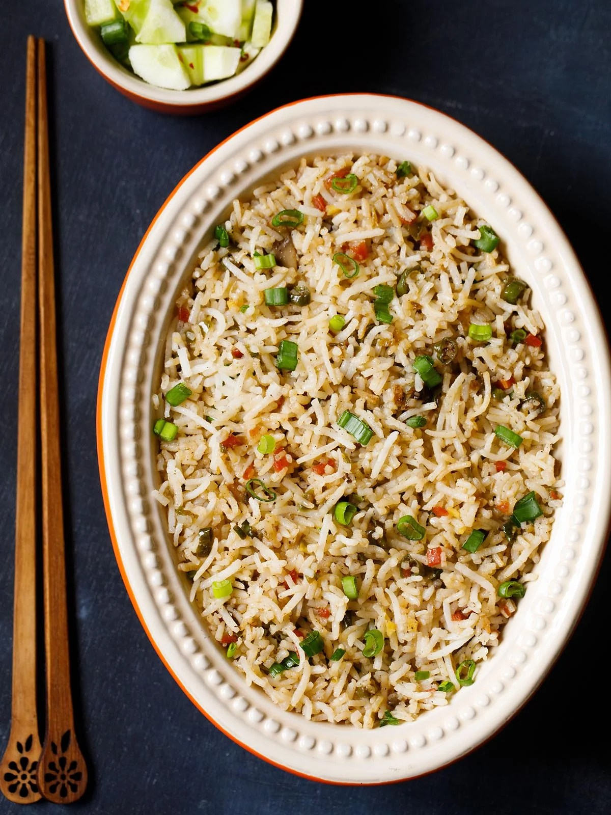 veg fried rice in an oval ceramic bowl with wooden chopsticks on a slate black board