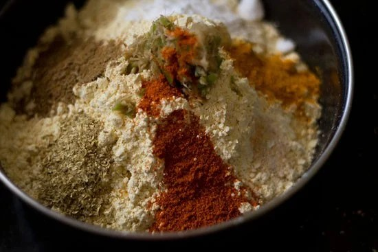 ingredients for the gram flour batter in a mixing bowl