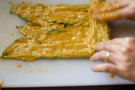 tightly roll the leaves and keep on apply the besan paste