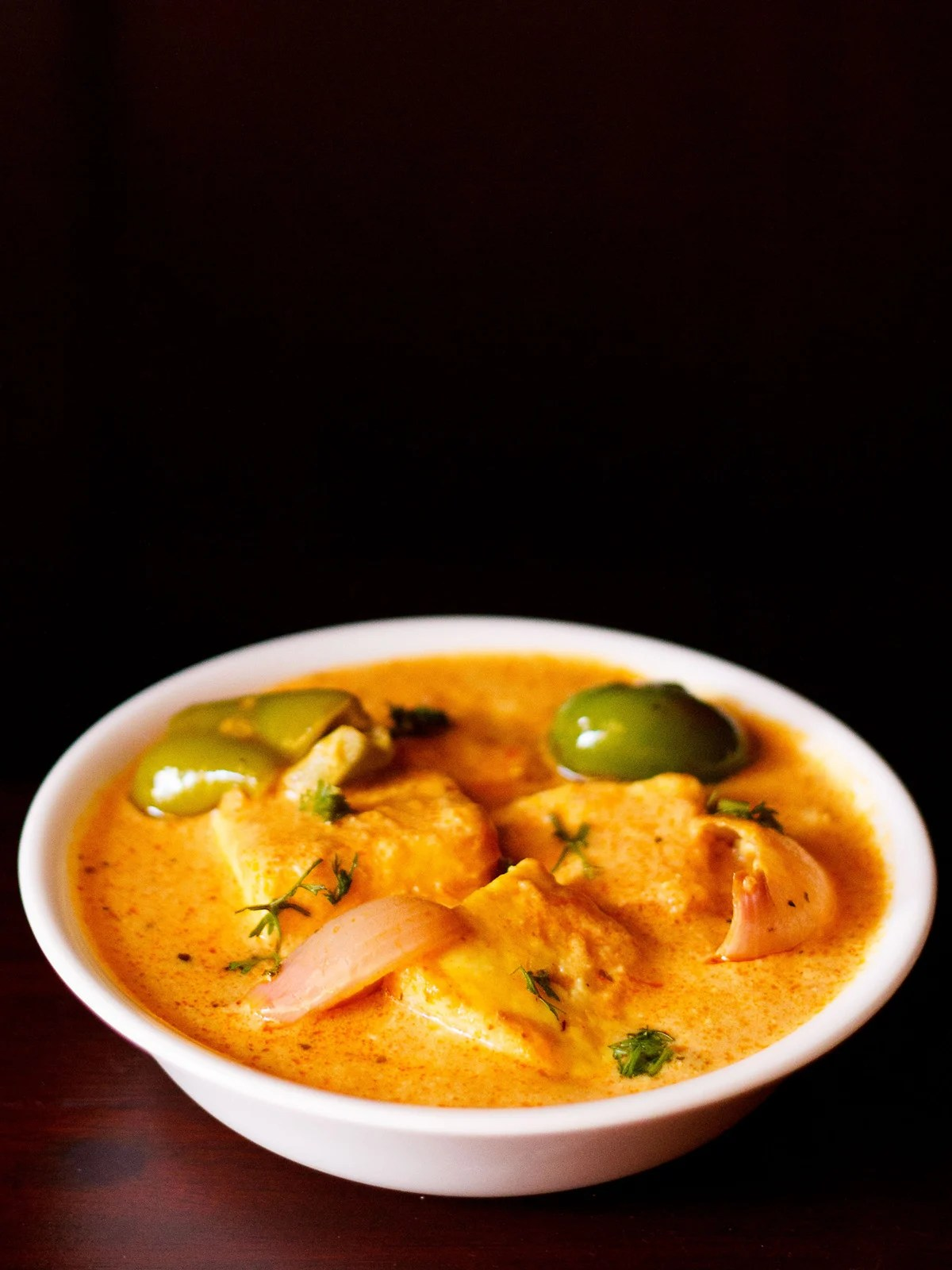 paneer tikka masala served in a white bowl garnished with some coriander leaves on a dark mahogany board