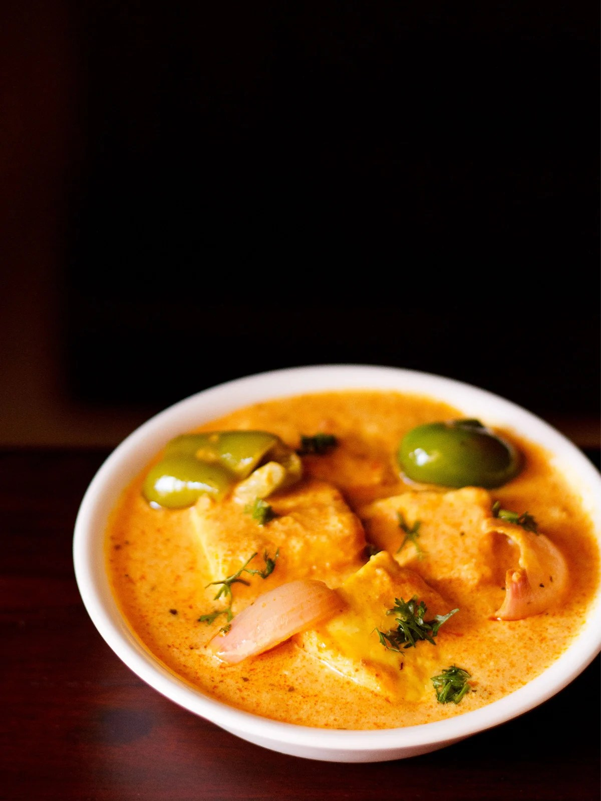 paneer tikka masala served in a white bowl garnished with some coriander leaves on a dark mahogany table