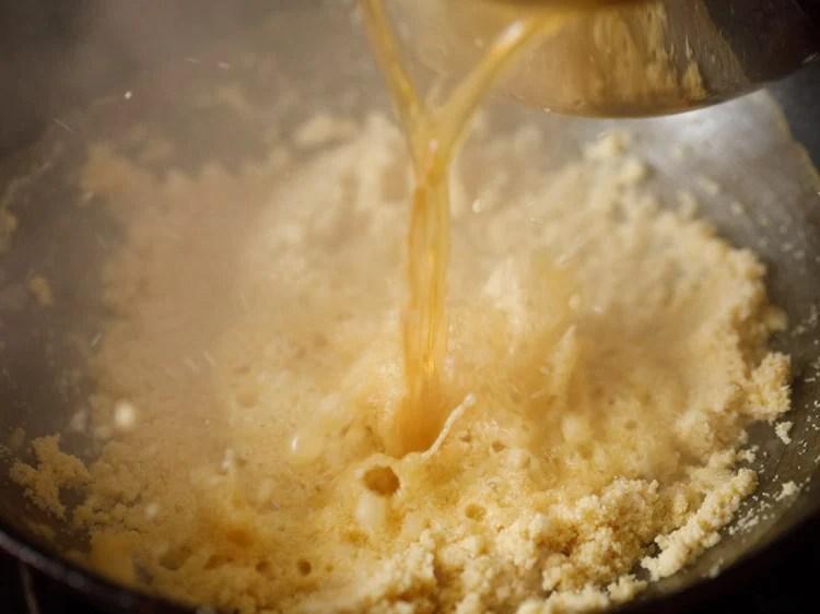 adding sugar solution to roasted rava