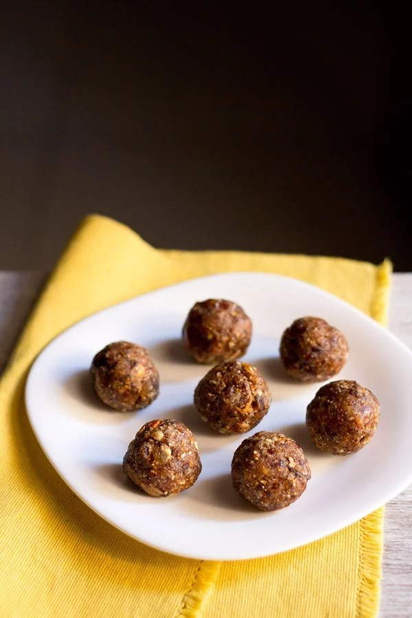 dry fruit ladoo placed on a white plate on a yellow napkin