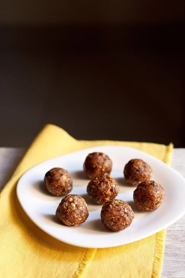 dry fruits ladoo placed on a white plate on a yellow napkin