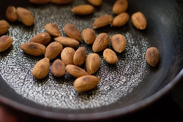 roasting almonds in a sliver-black dotted frying pan