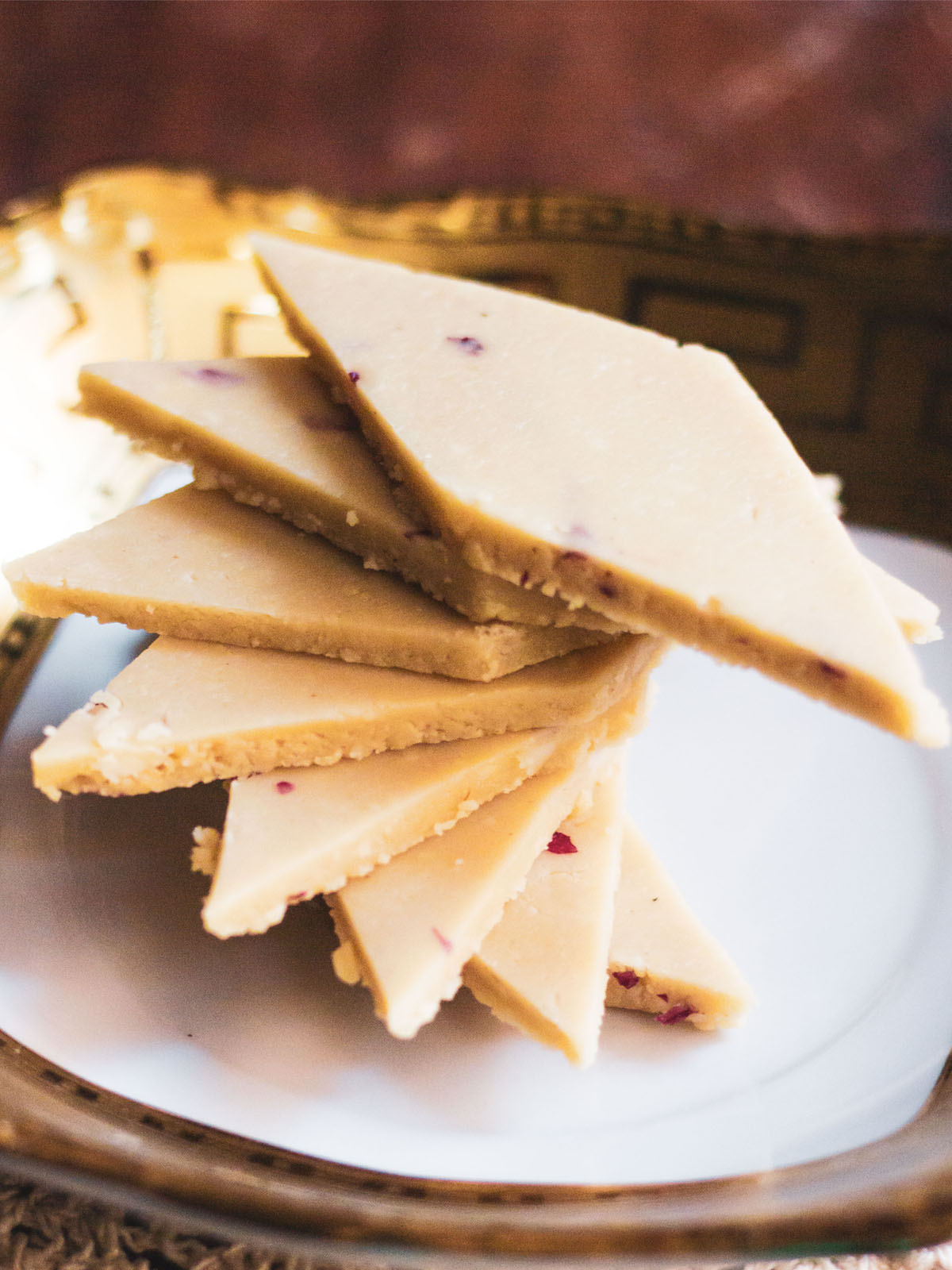 kaju katli stacked spirally on a golden rimmed white square plate