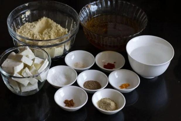 paneer pakora ingredients kept in various bowls on a black background