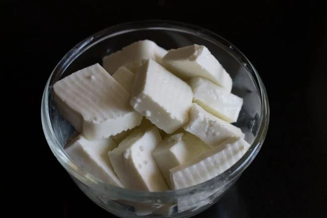 slices of paneer squares in a glass bowl