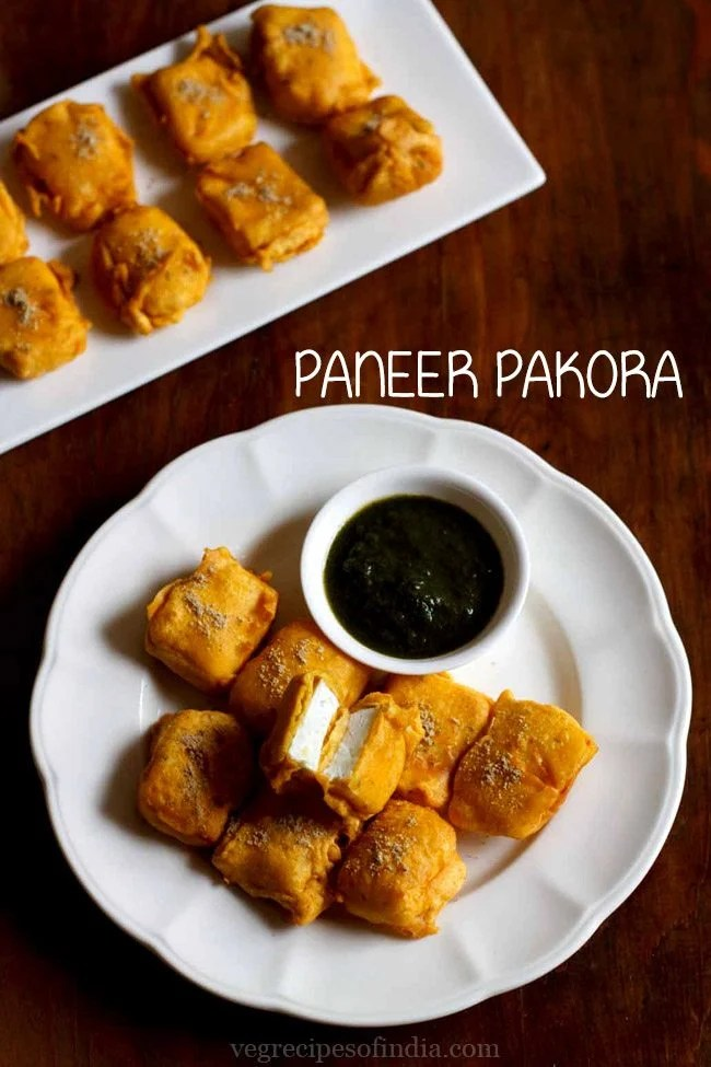 paneer pakora served in a white plate with green chutney in a small white bowl