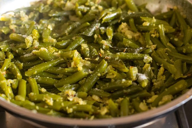 cooking french beans and stirring often