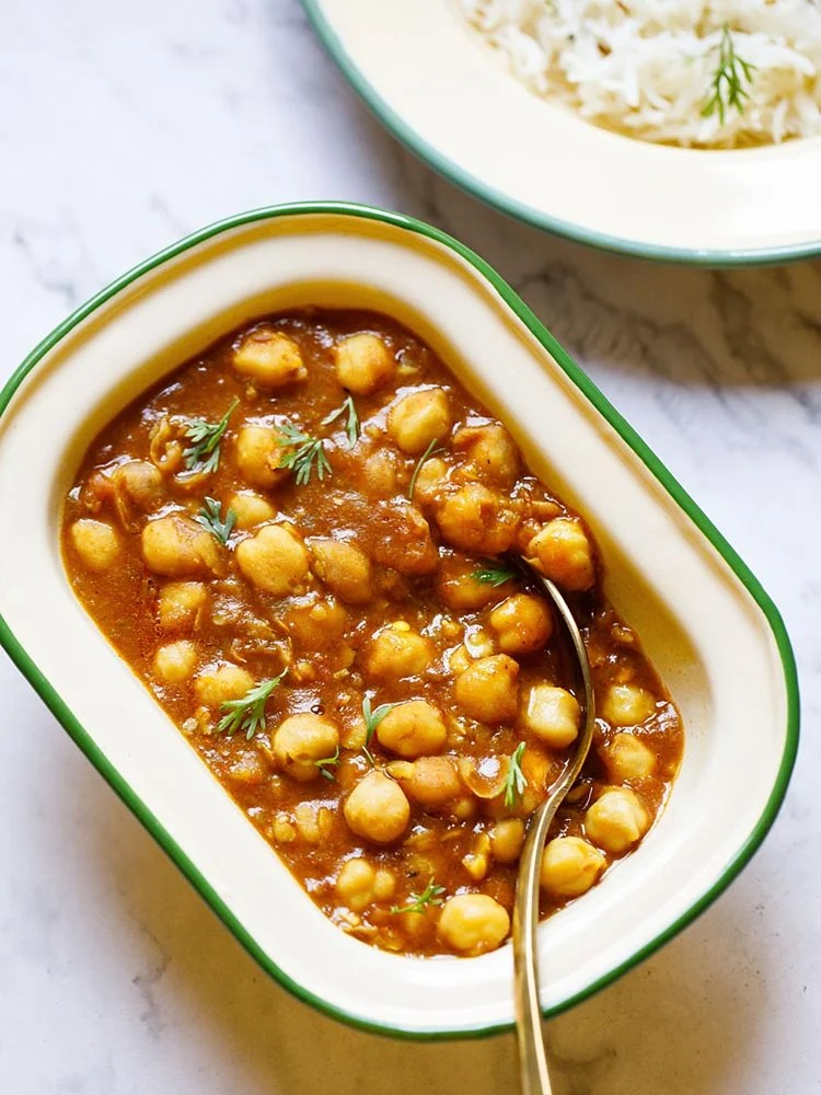 Instant Pot Chana Masala served in a rectangular enamel cream bowl with a green border with a brass spoon inside the bowl