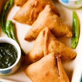 samosa arranged in a line on a cream tray with chutneys in small bowls and fried green chillies on the tray
