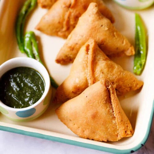 samosa kept in a cream tray with a bowl of green chutney and fried green chillies by the side