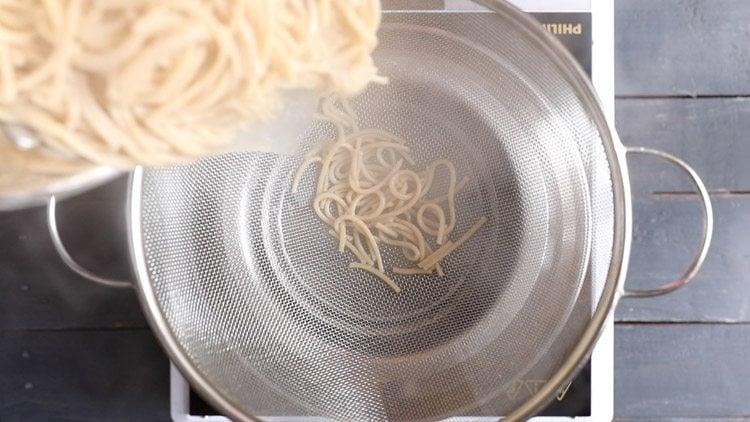 straining noodles in a colander