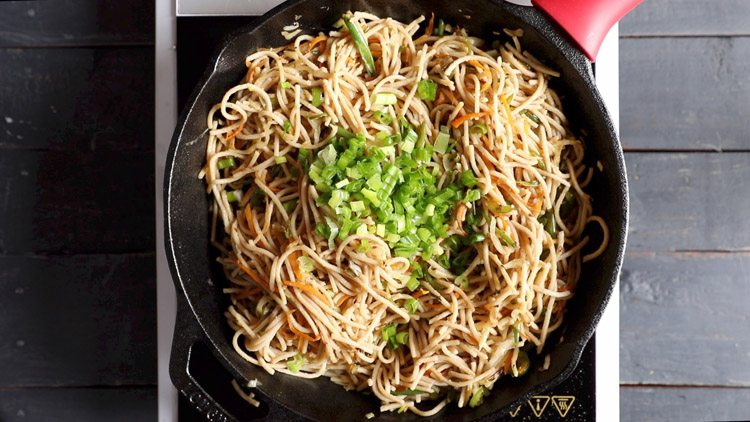 adding spring onions in veg noodles recipe