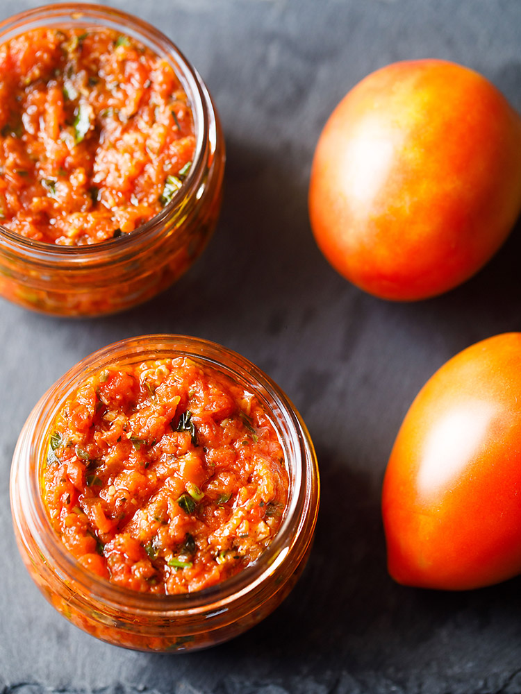 pizza sauce in two small glass jar placed on a dark gray slate board with fresh two tomatoes by the side