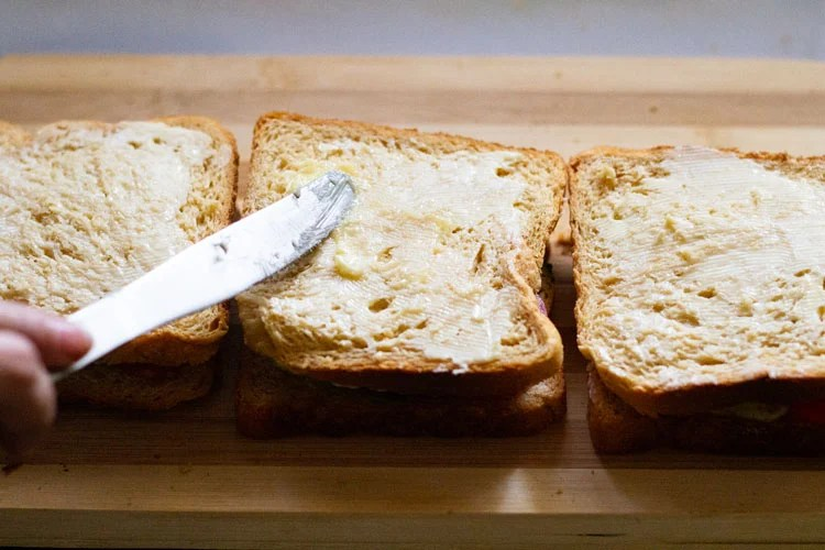 spreading butter on top side of assembled sandwich