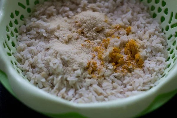 salt, sugar and turmeric powder added to poha