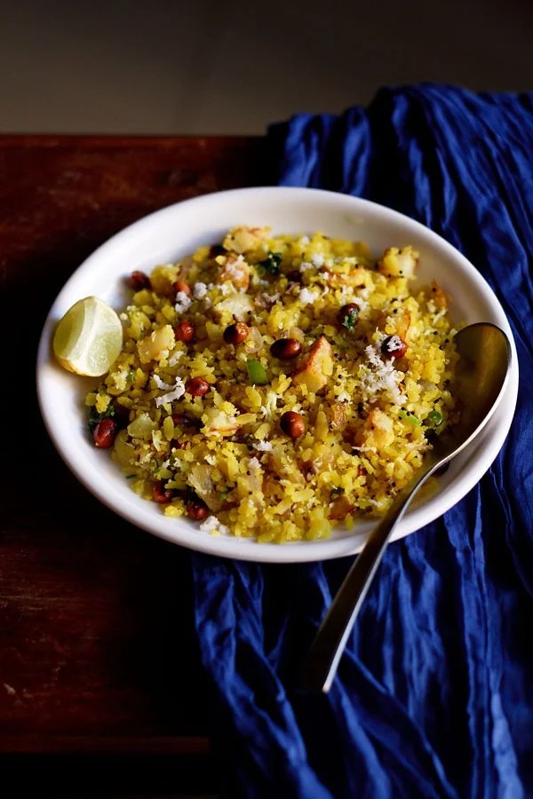 kanda batata poha in a white bowl with a side of lemon wedge and steel spoon on a dark blue fabric