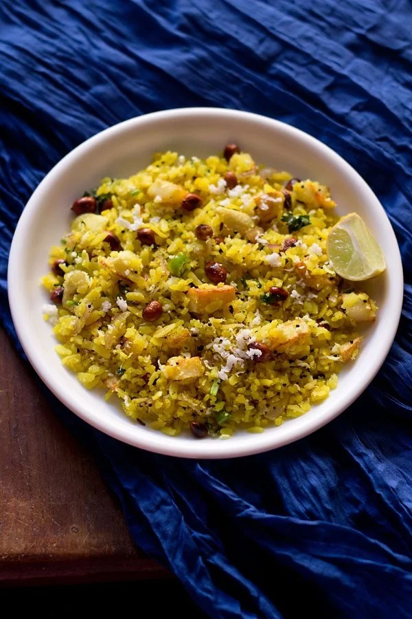 kanda batata poha in a white bowl or a dark blue fabric