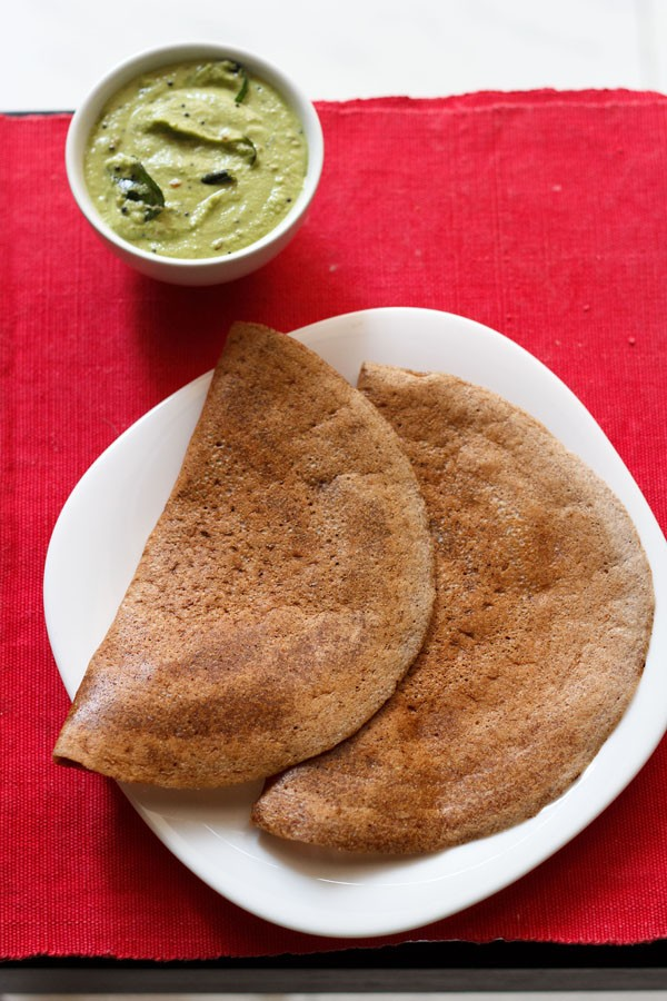 ragi dosa served on a white square plate on a red napkin with a side white bowl of green coconut chutney