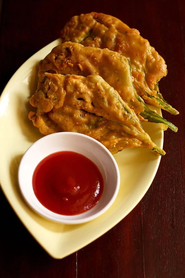crispy spinach leaf fritters placed on a light yellow oval plate with ketchup in a small white bowl