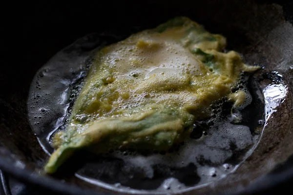 frying spinach fritters in oil in a pan