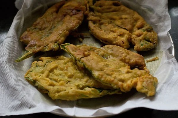 fried spinach fritters placed on kitchen paper towels