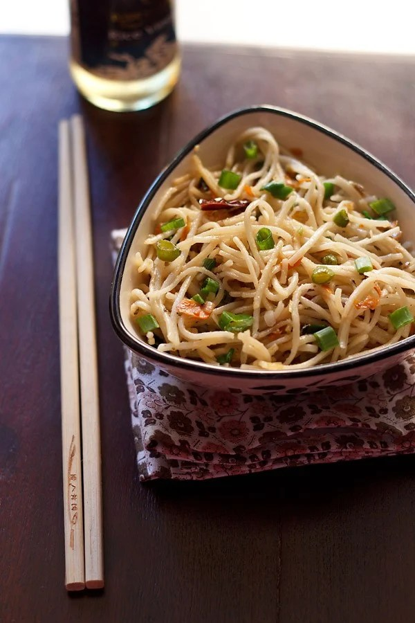 hakka noodles garnished with some spring onion greens and served in a triangular bowl on a printed napkin with cream colored bamboo chopsticks placed at the left side