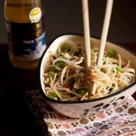 hakka noodles served in a triangular bowl on a printed napkin with cream colored bamboo chopsticks placed on top of the bowl with some hakka noodles between them